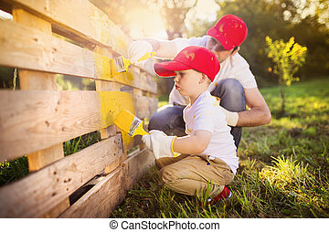 Father and son painting fence - Cute little boy and his...