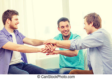 smiling male friends with hands together at home - teamwork,...