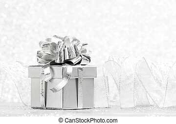 Gift box with tied to bow satin ribbon over bokeh background