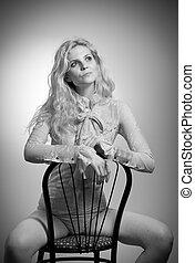 Blonde woman on chair, studio shot - Attractive fair hair...