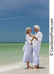 Happy Senior Couple Dancing Holding Hands on Beach