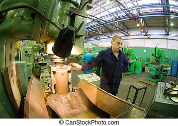 Young milling-machine operator works at machine