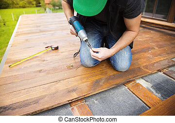 Handyman installing wooden flooring in patio, working with...