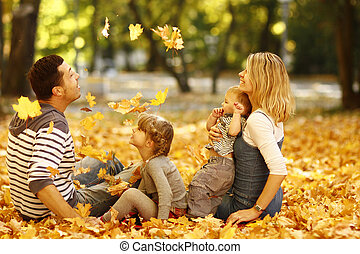 young family playing in autumn park outdoors