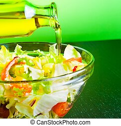 olive oil bottle pouring in the Italian fresh salad on green...