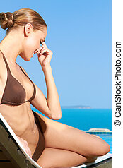 Smiling Woman in Brown Bikini on Beach Chair