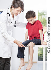 Childs neurologist testing knee reflex of young patient