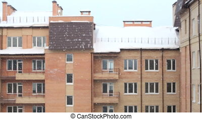 Snow against brick house.