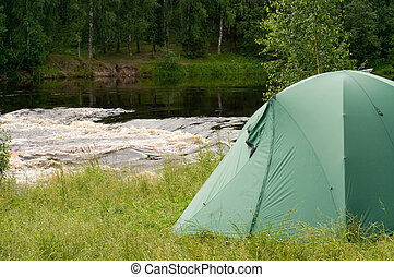 Campsite - Tent set up for camping in the wood by a river