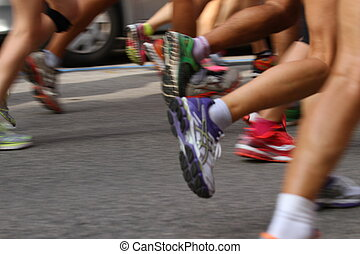 athletes during the marathon racing in the street - many...
