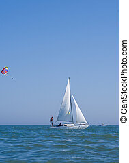 Sailboat and parasail - White sailboat travel along blue...