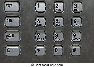 metallic number pad on a public phone - Close up image of a...