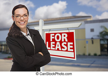 Woman In Front of Commercial Building and For Lease Sign -...