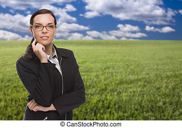 Confident Woman in Grass Field Looking At Camera
