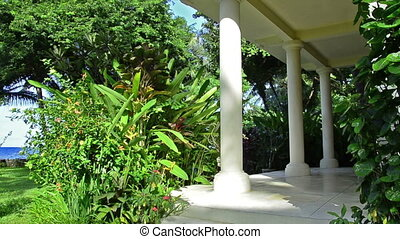 porch in tropical garden with white columns and ocean