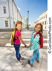 Two happy girls hold hands, stand near crossroad - Two happy...