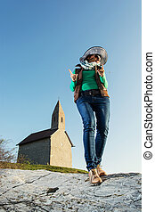 Young brunette in a stylish hat and an old romanesque church Arc