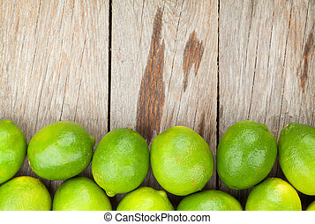 Fresh ripe limes on wooden table with copy space