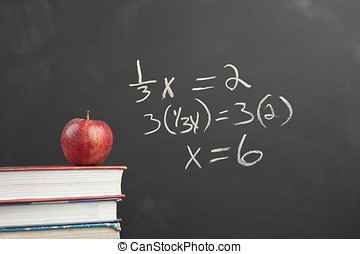 Red apple and algebra equation. - An apple on stack of books...