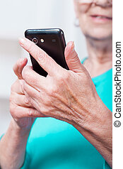 Senior woman sending text message - Hands of senior woman...