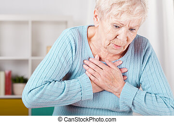 Elderly woman having heart attack - Portrait of elderly...