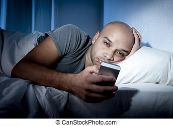young cell phone addict man awake at night in bed using...
