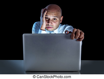 young stressed businessman working on computer laptop late...