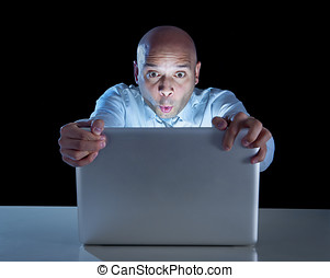 businessman alone at night sitting at computer laptop...