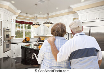 Senior Couple Looking Over Beautiful Custom Kitchen
