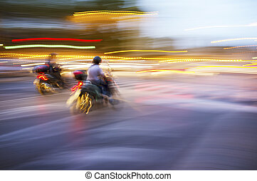 Scooters - Abstract blurry image of a scooters driving at...