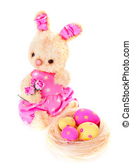 Rabbit bunny toy with eggs on the nest isolated in hand -...