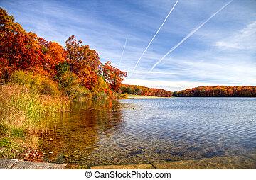 Autumn Lakeshore - Lush fall foliage frames the shore of a...
