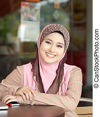 Muslim young girl smile at the coffee table