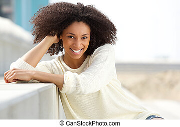Smiling african american woman with curly hair sitting...