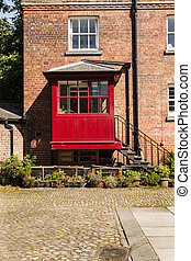 Courtyard with redbrick house and iron steps leading to a...
