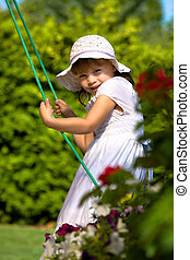 a closeup portrait of a young girl on a swing - a closeup...