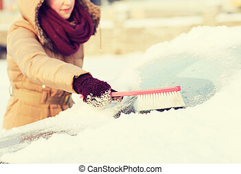 woman cleaning snow from car back window - transportation,...