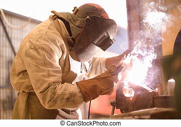 Arc Welder - Arc welder on work with protective helmet