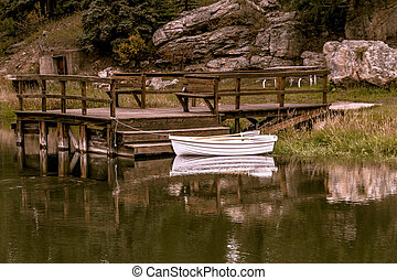 Small row boat sitting in pond - Small white row boat tied...