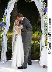 Newly-married couple in park on a background of an arch...