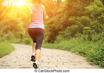 young woman running on forest trail - young fitness woman...