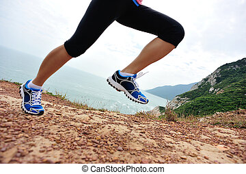young fitness woman runner legs running on seaside mountain...