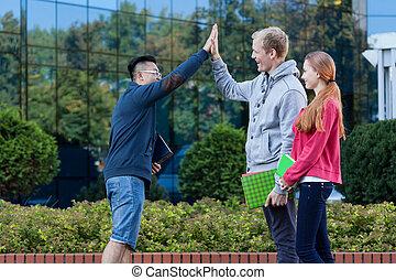 Asian boy giving friend five - Asian boy giving friend a...