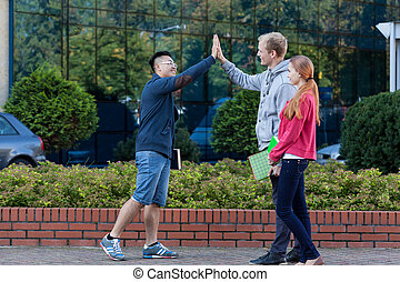 Asian young man giving friend five - Asian young man giving...
