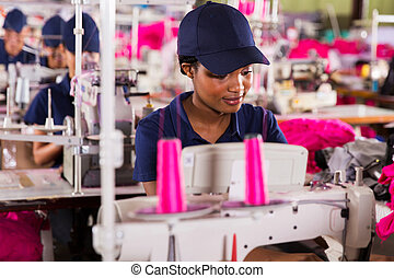 african clothing factory worker sewing with colleagues on...