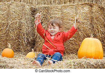 Baby with pumpkins on a farm - Portrait of a cute funny...