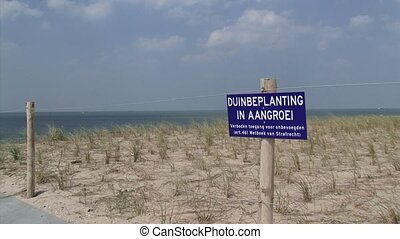 Sign in dunes - no trespassing, dune plants in growth in...