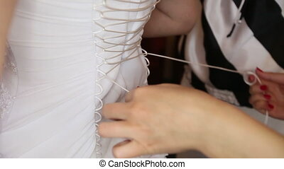 tightened bride corset on white wedding elegant dress