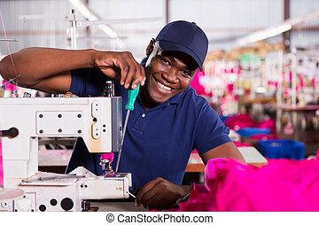 african american mechanic working in clothing factory