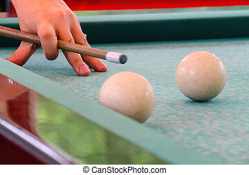 Hand with cue before the a blow to the billiard ball